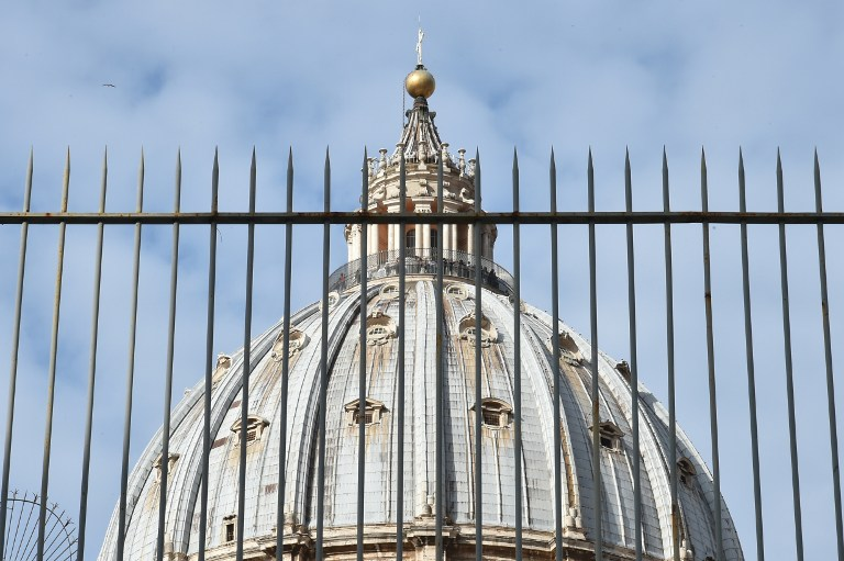 """A picture shows the cuppola of St Peter's basilica behind a fence on March 14, 2016 in Vatican during the """"Vatileaks"""" trial of two journalists and three former Vatican officials.  A controversial Vatican trial of journalists and alleged whistleblowers resumes today, in the latest instalment of an image-bruising legal saga. The spicy courtroom drama has already served up claims of sexually charged scheming, blackmail and computer hacking behind the fortified walls of the secretive city state.  / AFP / ALBERTO PIZZOLI"""