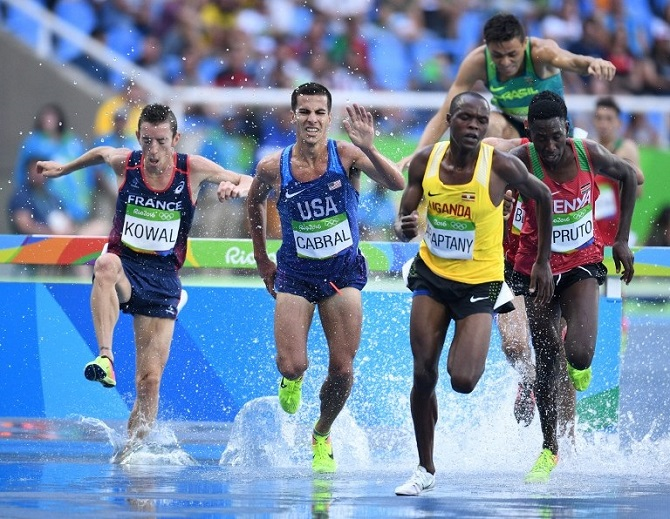 France's Yoann Kowal (L), USA's Donald Cabral (C) and Uganda's Jacob Araptany (2ndR) compete in the Men's 3000m Steeplechase Round 1 during the athletics event at the Rio 2016 Olympic Games at the Olympic Stadium in Rio de Janeiro on August 15, 2016. PHOTO AFP