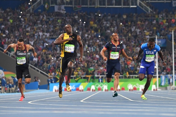Jamaica's Usain Bolt (2ndL) reacts after he crossed the finish line head of USA's Justin Gatlin (R), Canada's Andre De Grasse (L) and France's Jimmy Vicaut to win the Men's 100m Final during the athletics event at the Rio 2016 Olympic Games at the Olympic Stadium in Rio de Janeiro on August 14, 2016. AFP PHOTO
