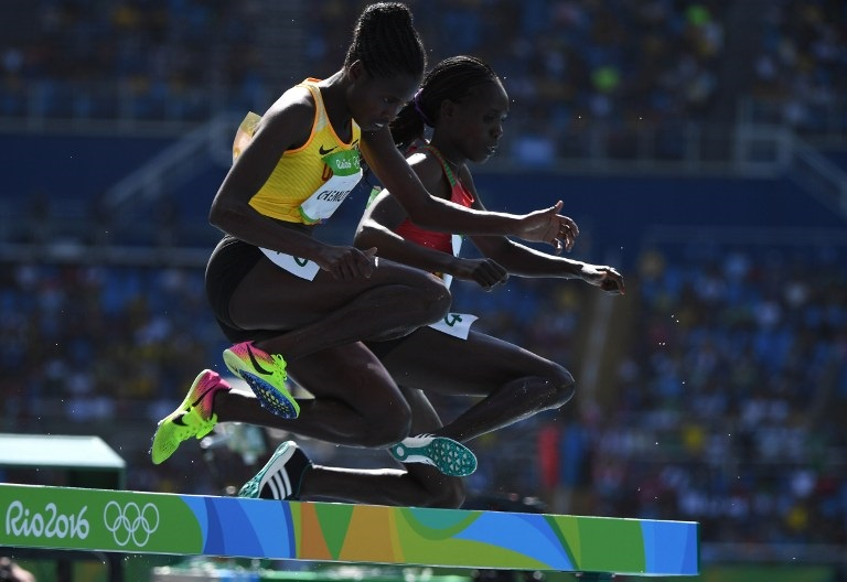 Uganda's Peruth Chemutai (L) competes in the Women's 3000m Steeplechase Round 1 during the athletics event at the Rio 2016 Olympic Games at the Olympic Stadium in Rio de Janeiro on August 13, 2016. / AFP PHOTO / OLIVIER MORIN