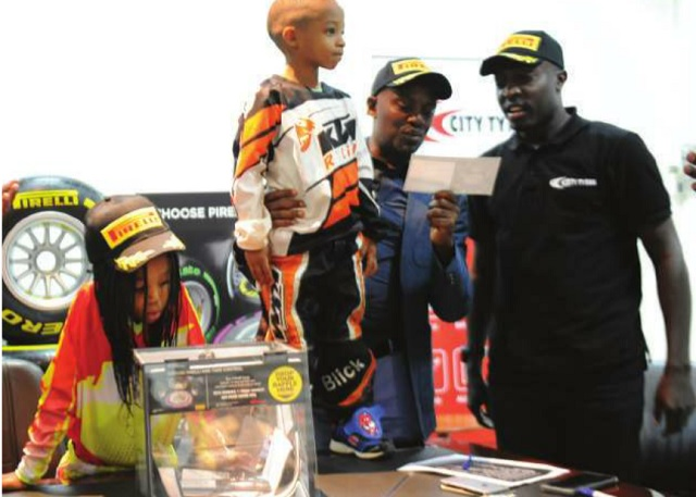 The Independent MD Andrew Mwenda (M) announcing the winner of the trip to the Formula one grand prix in Abu Dhabi. Right is City Tyres Marketing Manager Herbert Bashaasha and left is Isabella Blick, Africa Motor Cross junior champion.