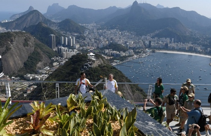 Bearers Diego Scofano (L) holds the Olympic Torch of Rio 2016 Olympic Games during a torch relay with Giuseppe Pellegrino atop the Sugarloaf in Rio de Janeiro on August 5, 2016.  PHOTO AFP