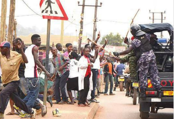 Police cane by-standers as they waved at FDC's Kizza Besigye after he had been freed from prison. File photo