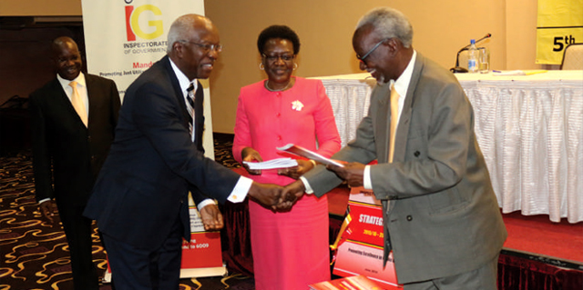 Kirunda Kivejinja (R), the second Deputy Prime Minister and Minister of East African Affairs gives a copy of the IG's new investment strategic plan to John Muwanga,